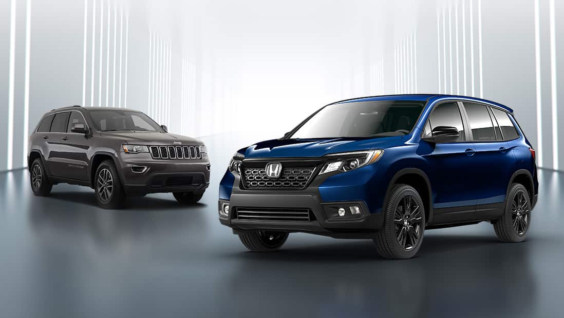Front 3/4 driver's side view of 2019 Honda Passport in Obsidian Blue Pearl parked in studio environment next to Jeep Grand Cherokee
