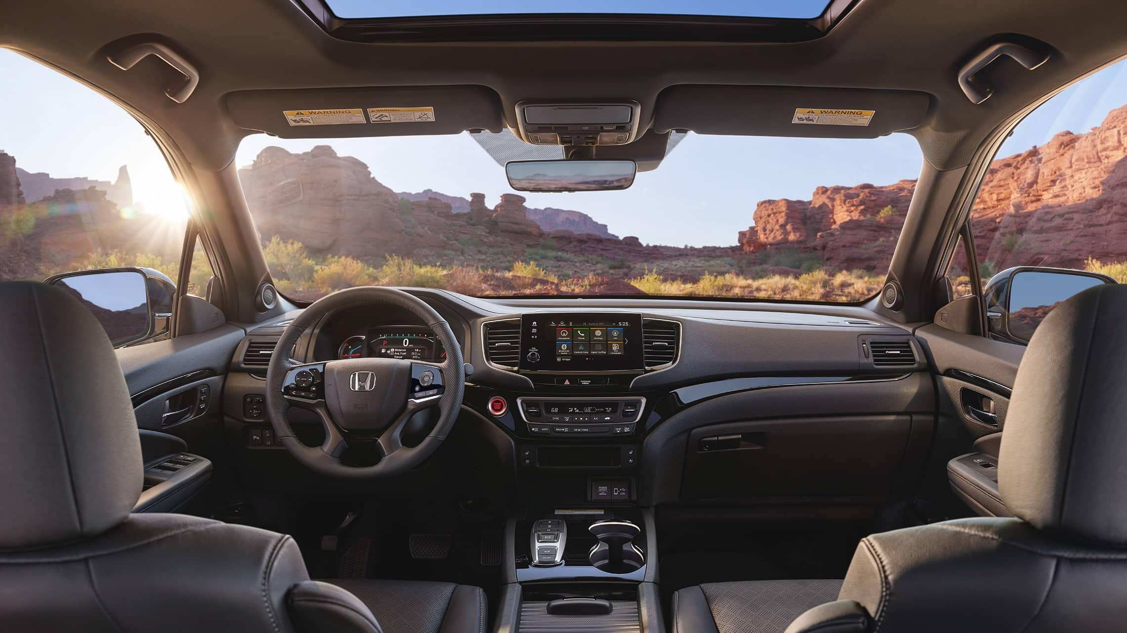 2019 Honda Passport Elite interior view with Black Leather interior showing the major instrument panel, featuring Apple CarPlay™ integration on the Display Audio touch-screen.