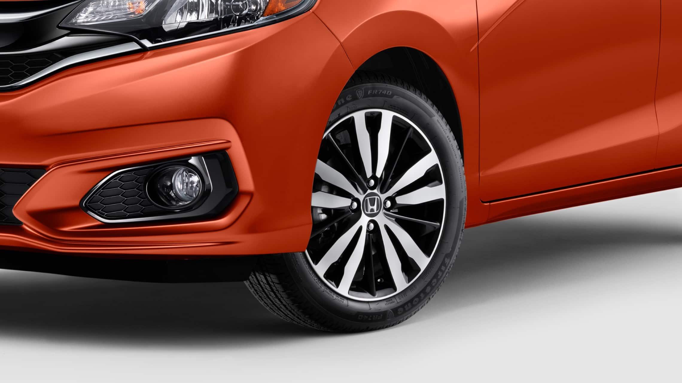 Vista frontal desde el lado del conductor del detalle de la rueda de aleación de 16pulgadas del Honda Fit EX-L2020 en Orange Fury.