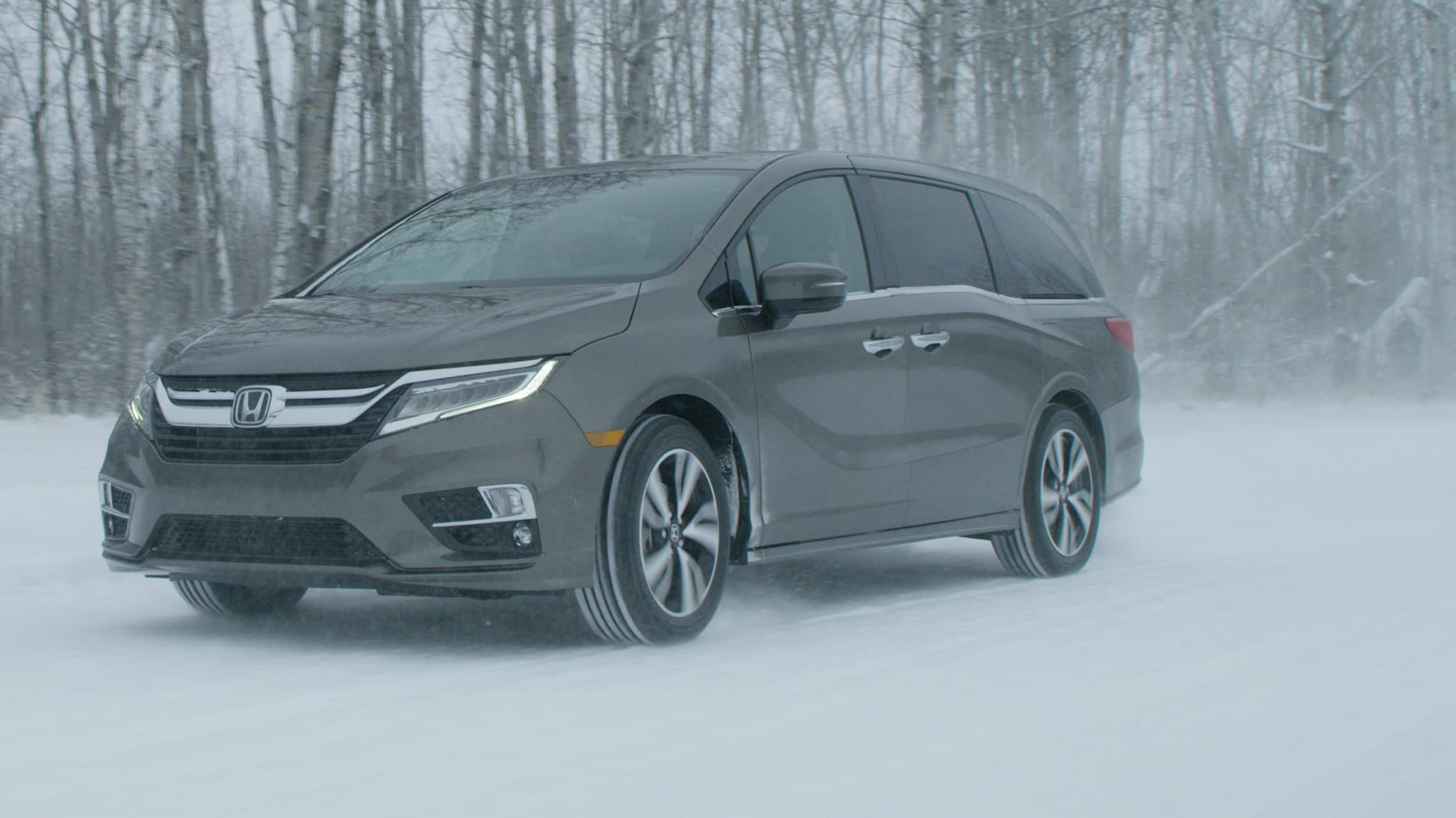Front 3/4 driver-side view of 2020 Honda Odyssey in Modern Steel Metallic driving on snow covered road.