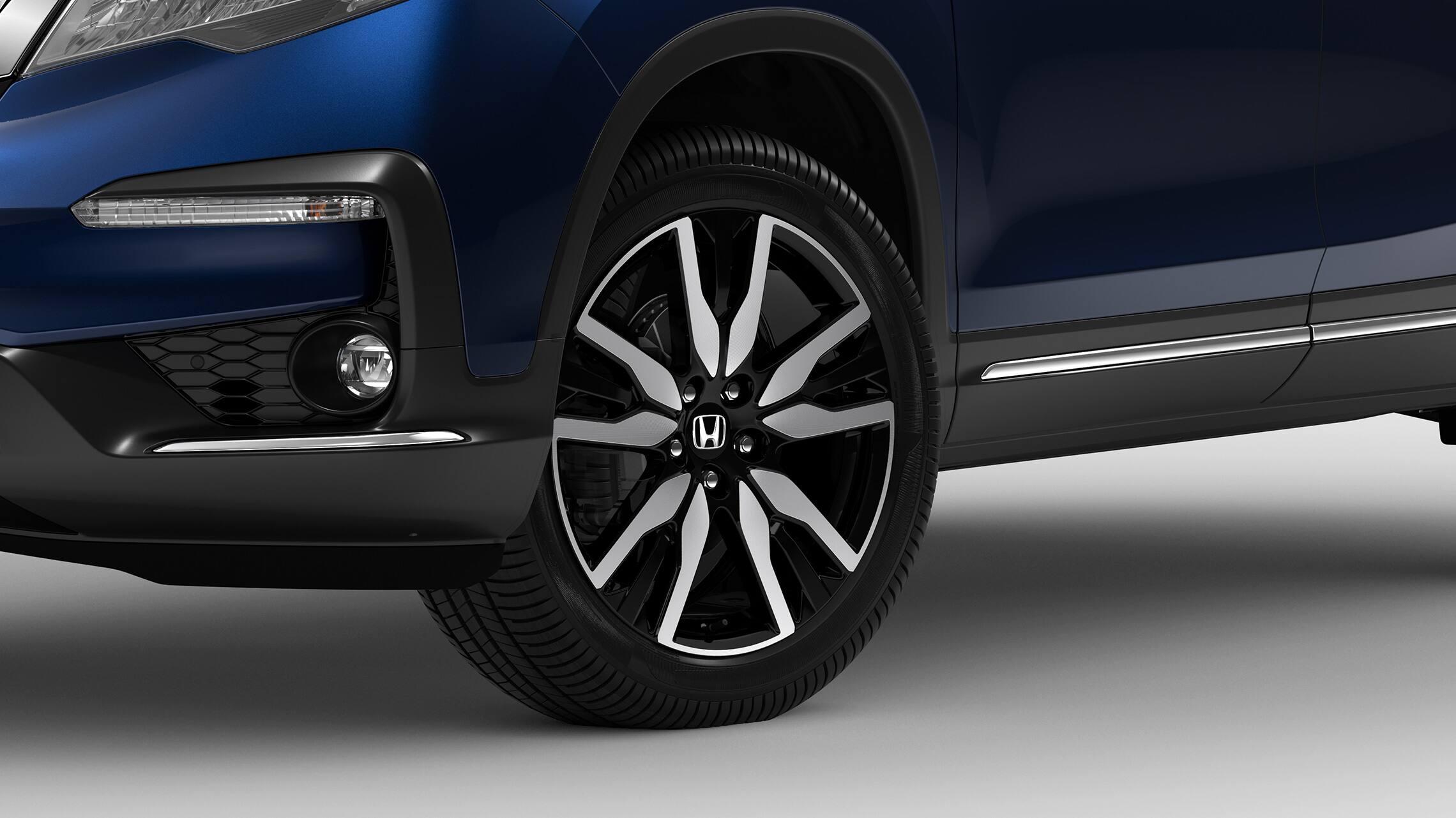 Vista frontal en primer plano de 3/4 desde el lado del conductor de la rueda de aleación de 20pulgadas y detalle del neumático en la HondaPilotElite2020 en Steel Sapphire Metallic.