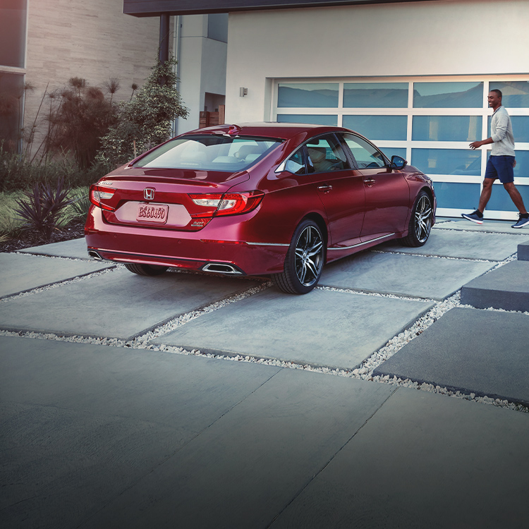 Seven-eighth rear passenger-side view of the 2021 Accord Touring 2.0T, shown in Radiant Red Metallic, parked on a driveway in front of a modern family home.